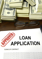 Approved loan application and dollar bills