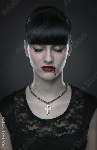 Beautiful gothic vampire woman portrait over dark background
