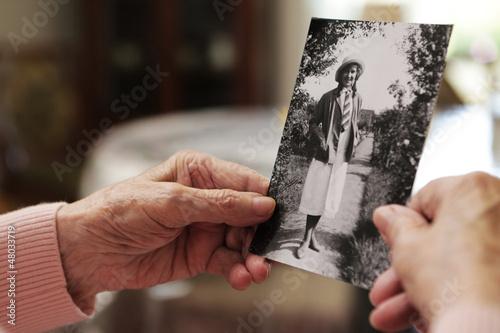 Leinwanddruck Bild Seniorin mit altem Foto aus ihrer jugend