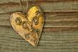 Goldenes Herz aus Metall auf Holzhintergrund