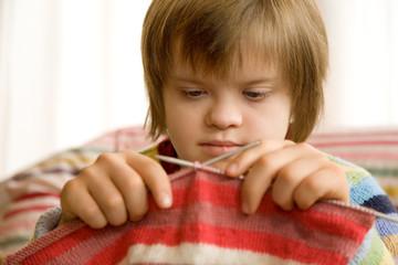 fille trisomique tricotant