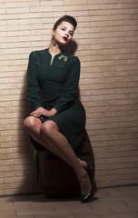 Retro Style. Pin-up Girl in Green Dress on Barrel - Brick Wall