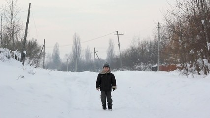 the boy is on the road in winter,boy goes,