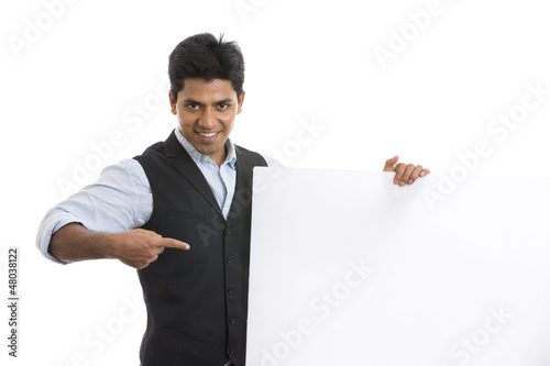 Smart Indian young businessman posing with white board
