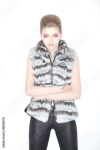 Trendy Woman in Fur Waistcoat and Leggings Posing in Studio
