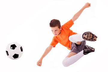 Boy making a acrobatic kick with soccer ball, isolated on white