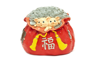 Coin pile up and two little pig in red bag, isolated