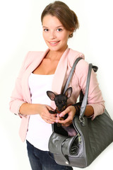 Smiling young woman with Chihuahua in a bag isolated on white ba