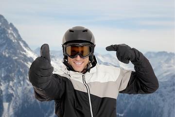 Skifahrer deutet auf Helm mit Daumen hoch im Skigebiet