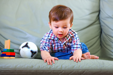 curious little baby boy on couch
