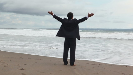 man in official suit standing on the sea coast
