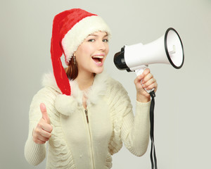 Young girl  in santa  hat with a speaker showing ok