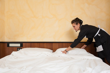 Chambermaid woman changing sheets in a hotel room.