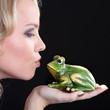 Frau küsst Frosch mit Kussmund