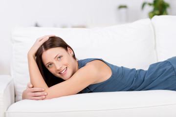lächelnde frau liegt auf dem sofa