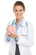 Smiling medical doctor woman holding piggy bank
