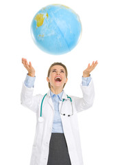 Happy medical doctor woman throws up globe
