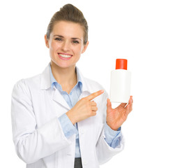 Smiling cosmetologist pointing on bottle of sunscreen