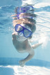 young child diving undwerwater in mask in pool