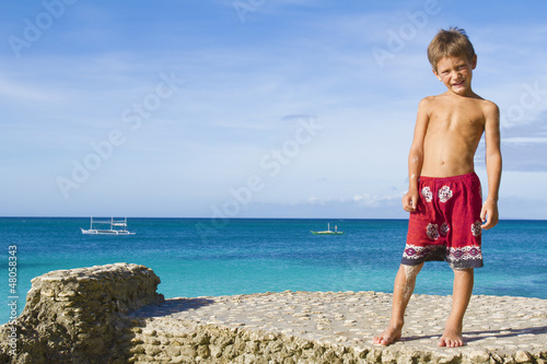 young happy child boy on rocks on tropical sea background