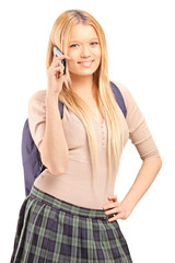 A blond female student with a school bag talking on a phone