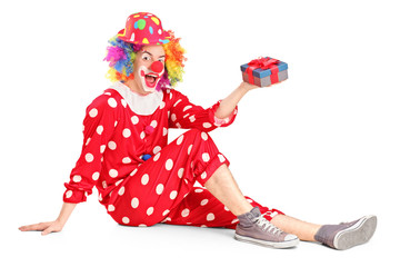 A smiling clown on a floor holding a gift