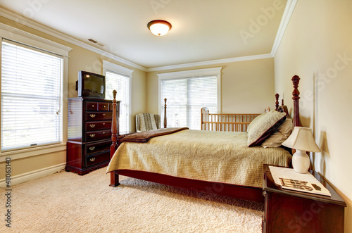 Large bright bedroom with wood furniture and beige tones.