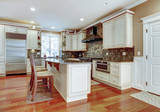 Large white luxury kitchen with cherry hardwood.