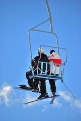 Sciatore e snowboarder sulla seggiovia