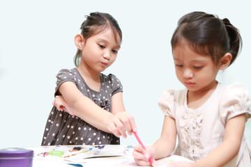 A Girl Tease Her Sister Doing Homework