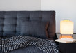 Cozy gray sofa, table lamp and book