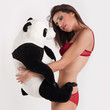 Smiling and sexy woman embracing teddy bear panda.