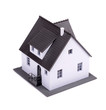 A model of house with dark roof on a white background.