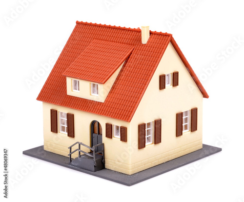 A model of house with red roof on a white background