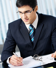 Portrait of writing smiling businessman working at office