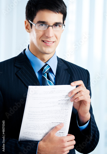 Businessman with document or contract, at office
