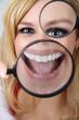 Junge Frau blickt lustig durch Lupe und reist Mund auf
