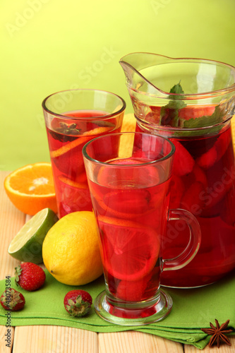 sangria in jar and glasses with fruits,