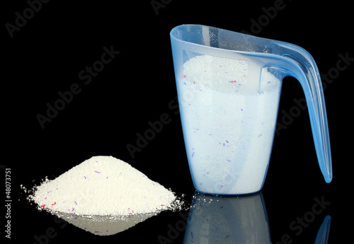 washing powder in a measuring cup, isolated on black