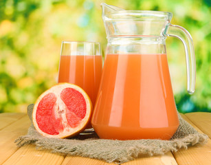 Full glass and jug of grapefruit juice and grapefruits