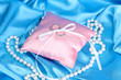 Wedding rings on satin pillow on blue cloth background
