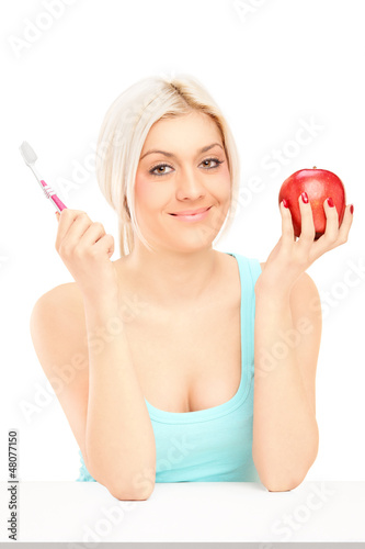 Beautiful blond woman holding red apple and tooth brush