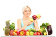 Beautiful woman holding apples behind a table full of fruits and