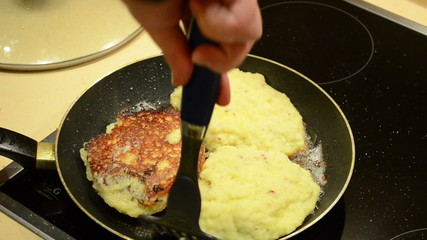 baking potato pancakes. hand turn upside pancakes and close pan