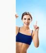 Woman in fitnesswear showing signboard, over blue
