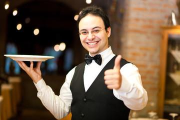 Positive waiter in an elegant restaurant