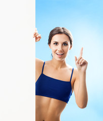 Woman in fitnesswear showing signboard, over blue