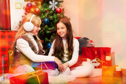 Two lovely girls under Christmas tree