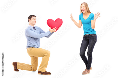 A smiling male kneeling with red heart and surprised woman