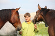 Teenager boy and horses from the herd